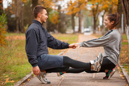 Young couple, athletes, train in an autumn park, crouch on one leg.