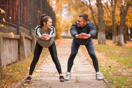 Young couple, athletes, train in the autumn park