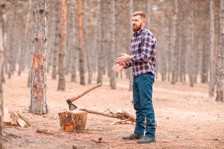 A lumberjack with a beard stands and shakes his hands of sawdust. A nearby ax sticks out in a pen. Outdoors. Stock Photo