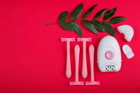 Close-up of epilator and disposable razor, on red background, top view.
