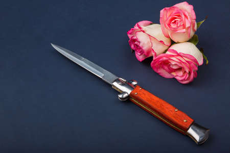Folding knife with an orange handle on a blue background with roses Stock Photo