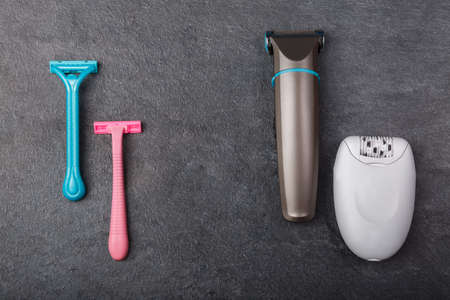 Razors, a depilator and a trimmer are on a gray background. Stock Photo - 90925343