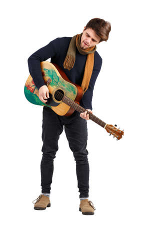 Handsome young man playing a guitar standing, with his head down, on an isolated white background.