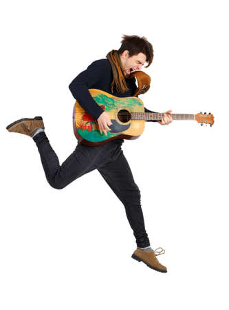 Handsome young man playing impulsively on guitar, jumping, on isolated white background.