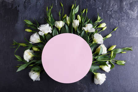 Japanese roses lie in a semicircle on a stone background. View from above