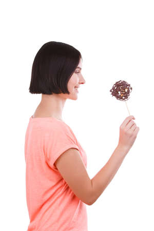 A girl is looking at a frozen chocolate on a stick on a white isolated background. Side view