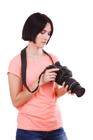 A girl looks at the panel on the camera in her hands on a white isolated background Stock fotó