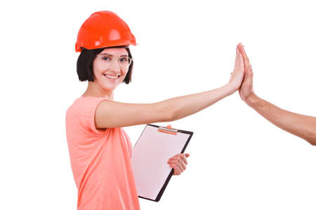 Girl contractor gives five and looks to the side on white isolated background