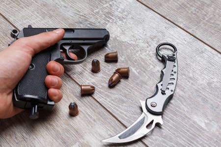The hand of the man holding a pistol, next to are cartridges and a knife.