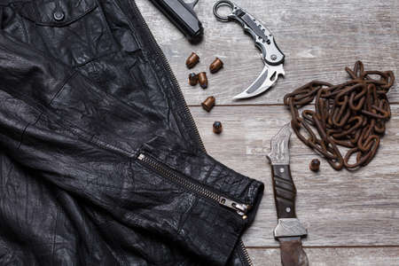 On the floor is a leather jacket, a chain, cartridges, a pistol and two knives. Stok Fotoğraf