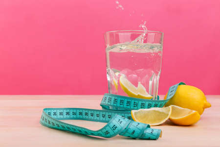 A glass of water with a slice of lemon, next to a whole and a few quarters of lemon and tape a centimeter. Stock Photo