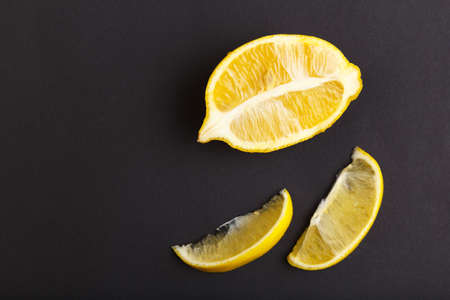 Half and two slices of lemon on a black background are. Vitamin C.