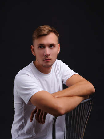 A young guy , sitting on a chair and looking into the distance. On a black background.