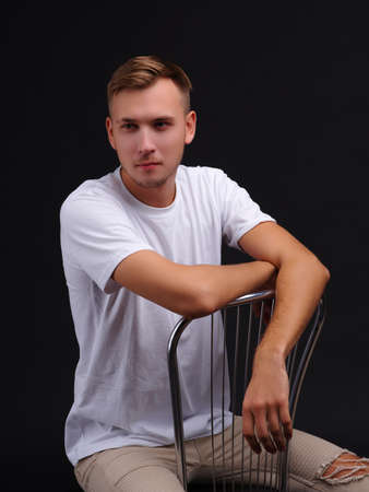 A serious guy, sitting on a chair, leaning his hands on the back of the chair. On a black background.