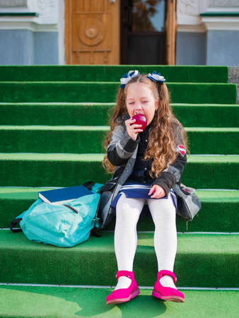 Little girl eating an apple on the doorstep of a school