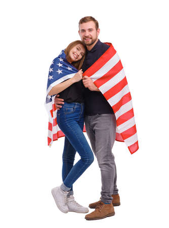 Portrait of young couple wrapped in American flag, isolated on white background.