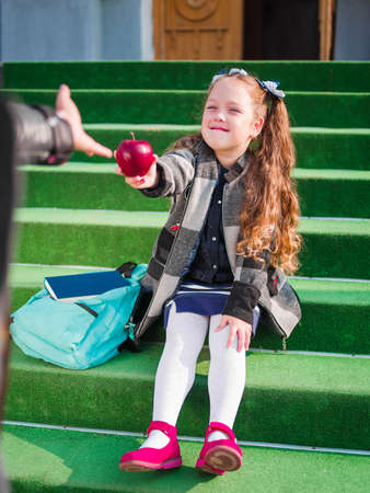 Little girl sitting on the doorstep of school, giving a red apple