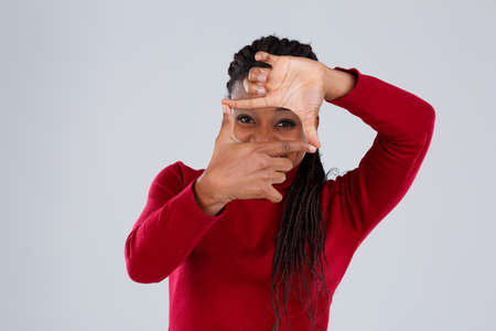 A girl folded fingers imitating a frame and looking through it and laughing.