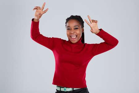 Happy African American girl dancing raising hands over head.