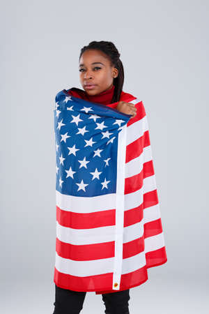A serious African-American girl covered with a American flag.