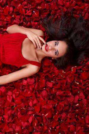 Girl lies in the red rose petals and holds fingers near mouth.