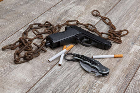 On the floor is a pistol, cigarettes, knife and an chain. Stock Photo
