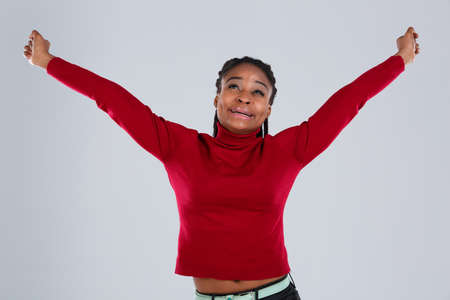 Afro American girl pulls up, lifting both hands up and smiling. Stock Photo