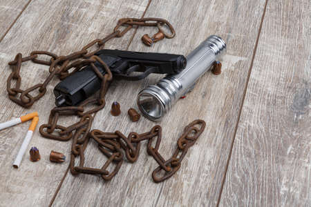 The layout of a pistol, several cartridges, two cigarettes, an rusty chain and a hand torch. Stock Photo
