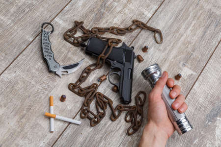The hand of man holding a torch, next to a pistol, a few ammunition, cigarettes, chain and a knife. Stock Photo
