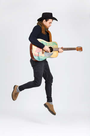 A guy in a hat jumps up while playing on a guitar. Isolated. Stock Photo