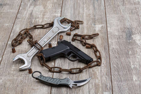 On the floor the layout is from an chain, a pistol, ammunition and a wrench.