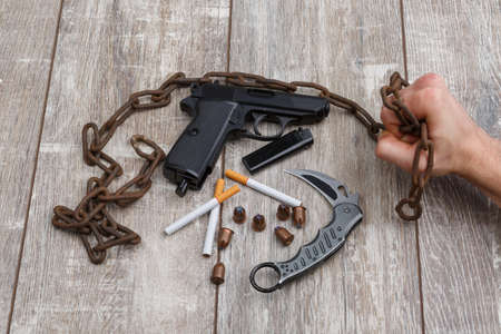 On the table, a man holding a rusty chain, next to pistol, a few ammunition, a knife and cigarettes.