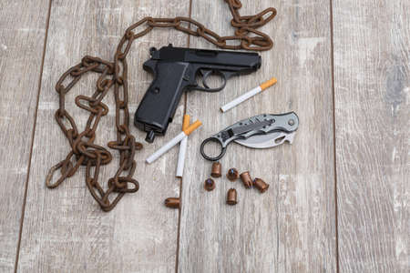 On the floor the layout is from chain, a pistol, ammunition, a knife and several cigarettes. Stock Photo