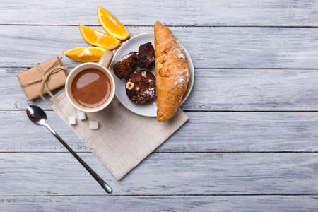 Close-up of a croissant, coffee, orange slices and a gift box, stand in the middle of a gray wooden background.