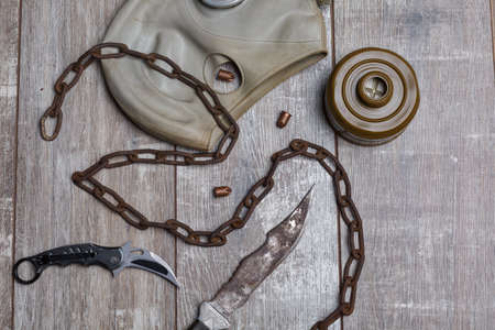 Gas mask disassembled with a rusty chain, with a folding and homemade knife on a wooden background Stock Photo