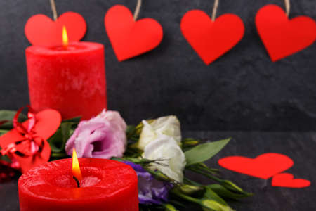 A burning candle in focus. Without focus a bouquet of Japanese roses, hearts on threads on a stone background