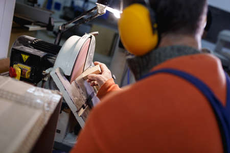 A worker in uniform in headphones stands with his back and grinds the bar on the machine in a blurred background