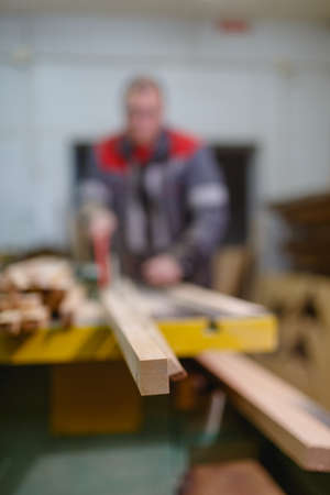 The finished part of the bar on the machine close-up on a blurred background with an employee and an instrument for hand safety