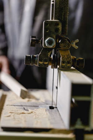 The hand holds a bar on the surface of the jig saw. Working part of the machine in a close-up. Front view Stock Photo