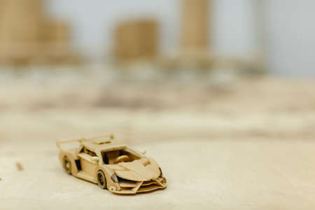 A wooden sports car on a wooden table on a blurred background Standard-Bild