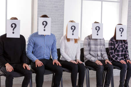 A group of people are sitting on chairs with closed faces, with a question mark next to them and their hands are on their knees Stock Photo