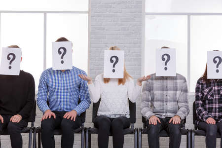 A group of people are sitting on chairs with closed faces, with a question mark next to them and their hands are on their . Front view
