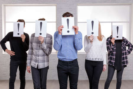 A group of people close their faces with sheets with an exclamation point. Stand next to an arrow Stock Photo