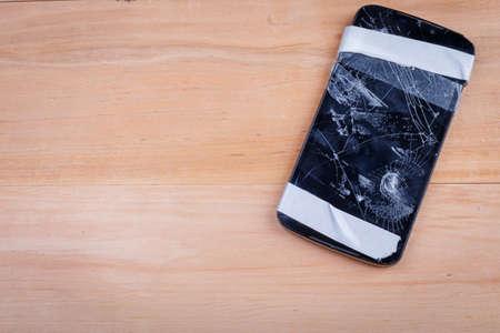 나무 바닥에 위쪽 및 아래쪽에 전기 테이프와 함께 깨진 된 전화. 위에서 본