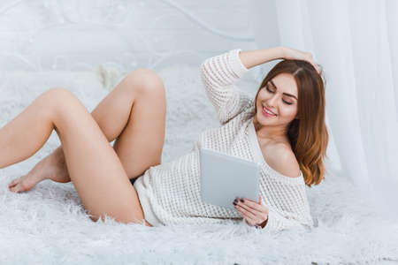 Girl with a tablet in her hand lies on a bed and straightens her hair on a white background