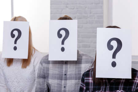 Three people with closed faces with sheets with a question mark