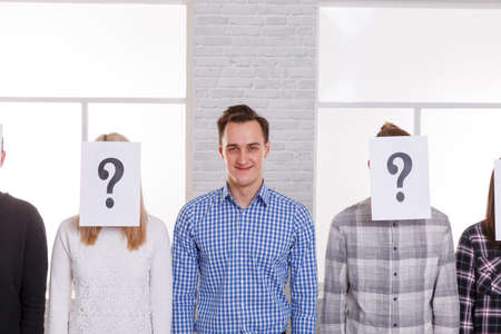A guy between people with closed faces with a leaf with a question mark