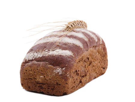 Roll of black bread with wheat ear top on white isolated background