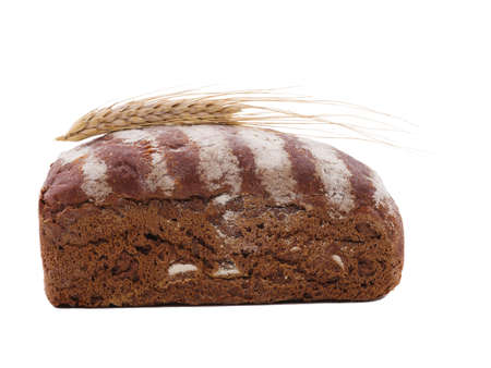 Roll of black bread with wheat ear top on a white isolated background. Side view