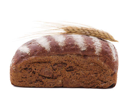 Roll of black bread with wheat ear top close-up on a white isolated background. Side view